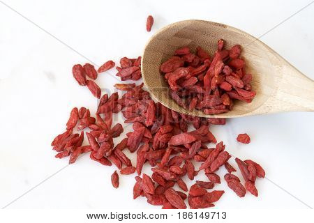 Goji berries and a brown wooden spoon.