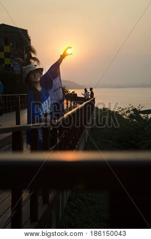 Asian Thai Woman Traveler Posing Catching The Sun For Take Photo At Riverside Of Mae Khong River In