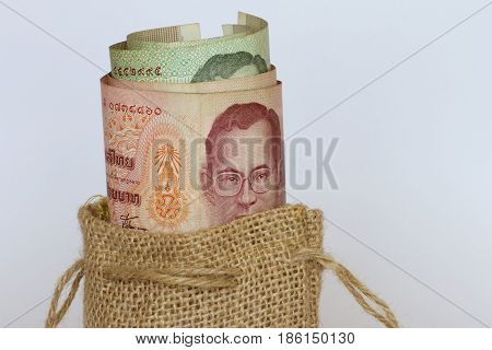 Thai notes in a brown hessian bag.