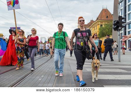 ZAGREB, CROATIA - JUNE 11, 2016: 15th Zagreb pride. LGBTIQ activists walking the dog decorated with rainbow colors.