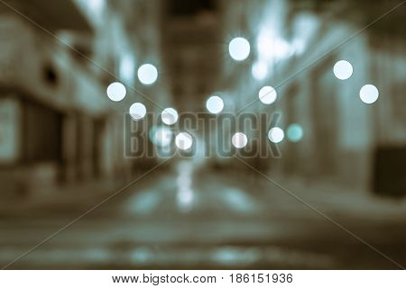 Background blue and brown tones retro effect lights in gritty street abstract street between blurry buildings at night long exposure blurred defocused image.