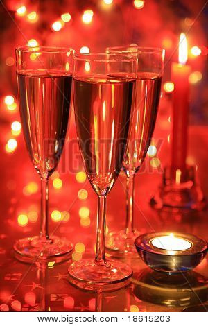 Champagne in glasses on red background