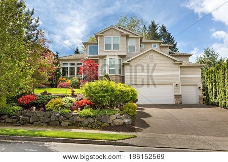 House with green lawn manicured frontyard garden in suburban residential neighborhood on a sunny day
