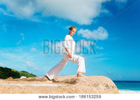 Photo of a young woman practicing yoga on the brach