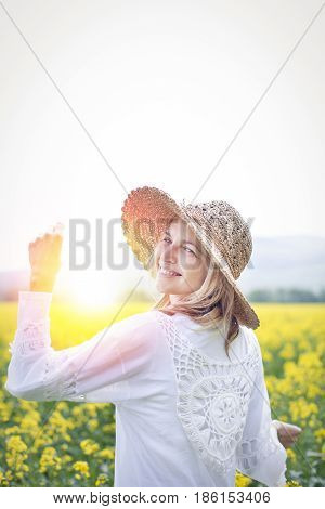 Woman with hat standing in yellow flowering rape field in summer with sun in background