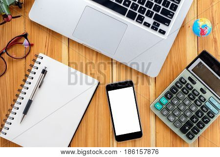 Office desk table with pen blank screen smart phone laptop leather notebook and calculator.Top view with .Supplies and gadgets on desk table.Working desk table concept.