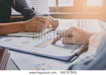 Image of two young business team writting notebook and graph financia at meeting.Close up business team analysis and strategy concept.