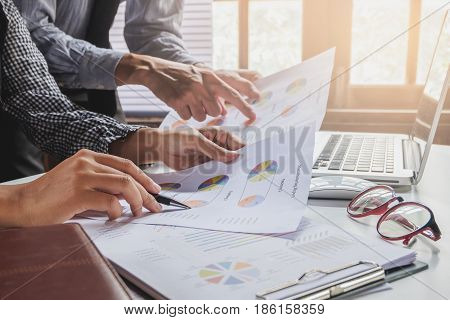 Image of two young business team using laptop computer and graph financia at meeting.Close up business team analysis and strategy concept.
