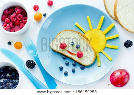 Creative breakfast idea for kids - bread bun with fruit and berry shaped funny cloud with peach sun and blueberry rain fun with food