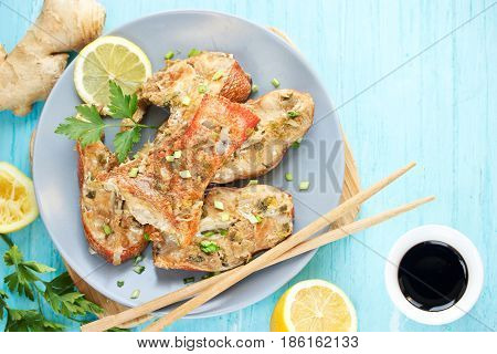 Steamed snapper (pacific ocean perch sea bass ruby perch) with soy sauce lemon ginger and parsley in Asian style. Healthy cooking