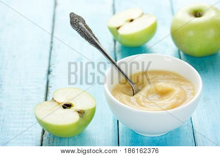 Healthy organic applesauce (apple puree mousse baby food sauce) in white bowl on table with green apples