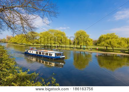 local cruise tour boat cruising along a river at Stratford upon Avon Warwickshire Enagland near Holy Trinity Church on a clear blue sky day