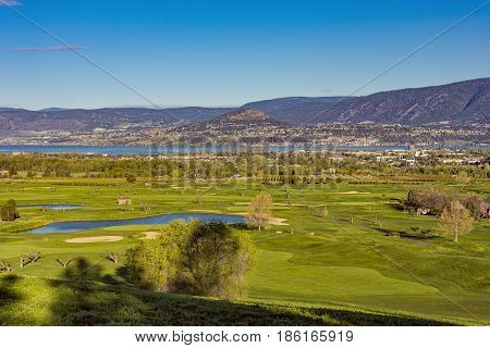 A golf course in the Okanagan Valley with the Kelowna British Columbia Canada skyline and Okanagan Lake in the background