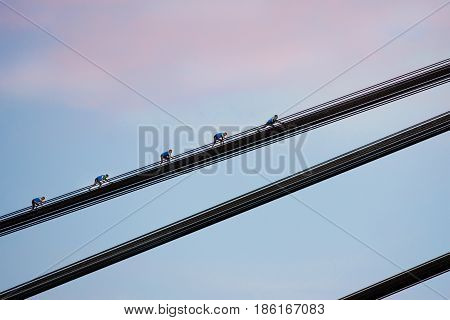 young brave woman roofer in the evening climing on the bridge