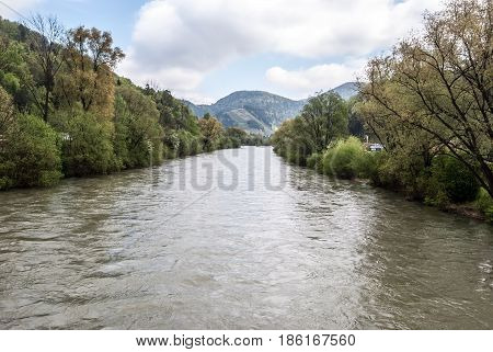 Vah river with trees around hills on the background and blue sky with clouds near Lubochna in Slovakia