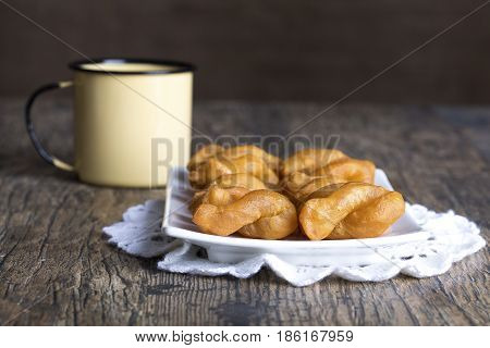 Metal mug full of coffee and a plate of koeksisters on brown wood table