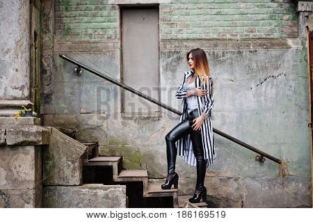 Fashionable Woman Look With Black And White Striped Suit Jacket, Leather Pants, Posing At Old Street