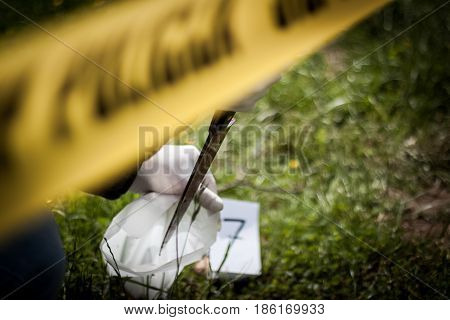The crime scene murder investigation police found a bloody knife in the grass and taken as evidence expert with rubber gloves is taken and placed in the bag