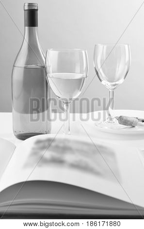 Wine bottle and two glasses behind an open book. The pages of the book are blurred, Vertical format in black and white.