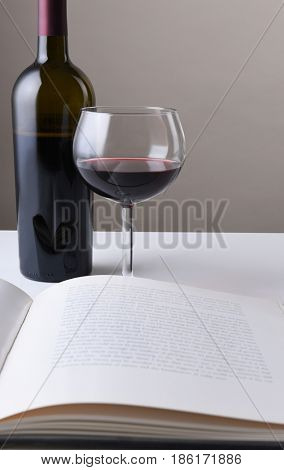 Wine bottle and glass behind an open book. The pages of the book are blurred. Vertical format with copy space.
