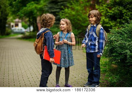 Little school students briskly and cheerfully talk on the schoolyard. Two boys and the girl have fun waiting for the beginning of occupations. Fine morning.
