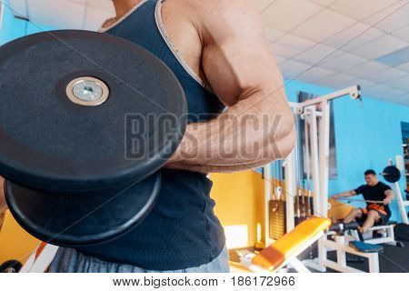 Male powerful biceps close-up. gym. Bodybuilder. A beautiful, inflated male body.