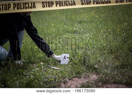 The crime scene murder investigation bloody knife on the grass an investigation is underway expert witness with gloves puts labels on the crime scene poster
