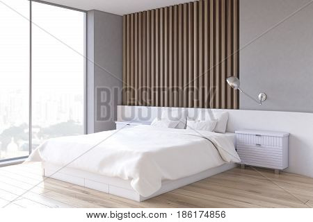 Side view of an interior of a bedroom with gray and light wooden wall element a double bed and two bedside tables. 3d rendering.