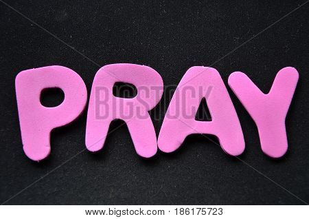 word pray on a  abstract black background
