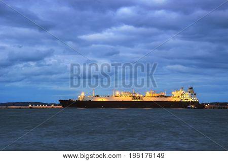 SWINOUJSCIE / POMERANIA BAY, POLAND - 2016: Illuminated LNG tanker moored to the gas terminal