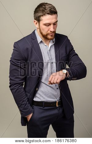 Handsome Well-dressed Man With Beard Looking At His Wrist Watch