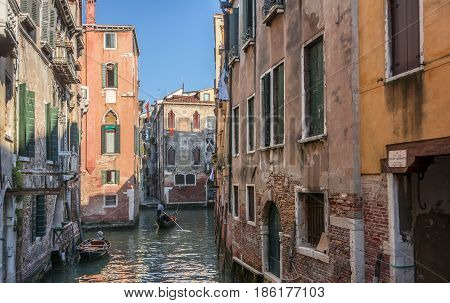 Venetian gondolier punting gondola through a small canal waters of Venice Italy.