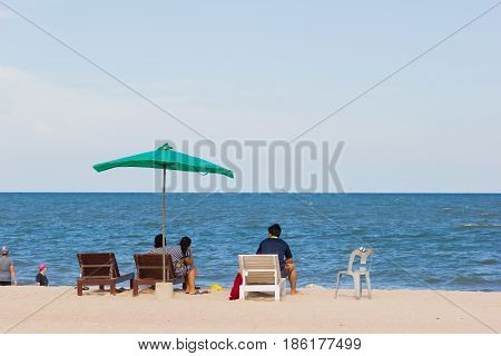 PHETCHABURI THAILAND - APRIL 7 : unidentified asian people resting on the sand beach with green big umbrella on April 7 2017 in Phetchaburi Thailand.