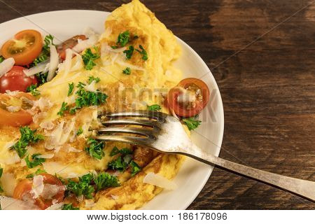 A photo of an omelette with cherry tomatoes, parsley. and grated cheese, shot on a rustic wooden texture with a fork and a place for text