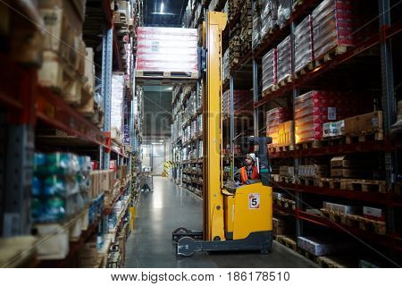 Loader lifting heavy cargo in warehouse