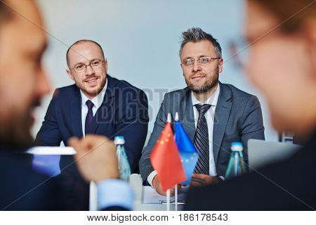 Two confident leaders listening to talk of their foreign colleagues