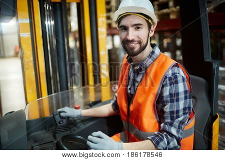 Warehouse loader in forklift truck looking at camera