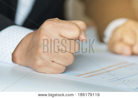 business people hand banging fist with angry on table problems stress workplace desk at office