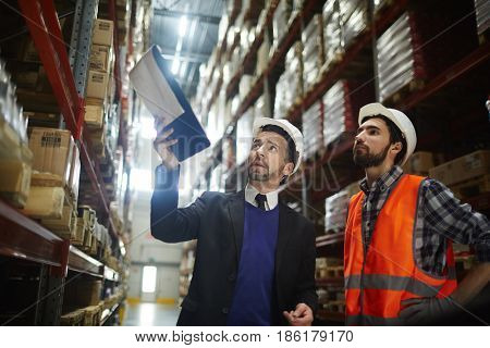 Two supervisors discussing amount of goods for export on shelves of warehouse