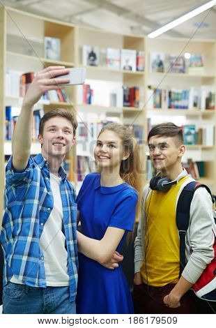 Group of college buddies making selfie in library