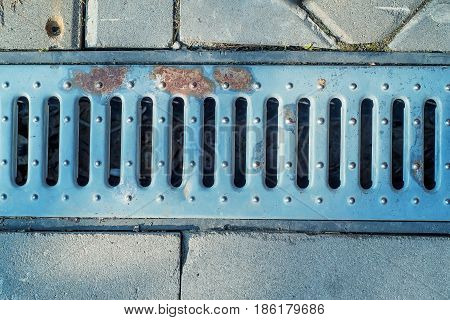 Close-up shot of storm drain grate on road