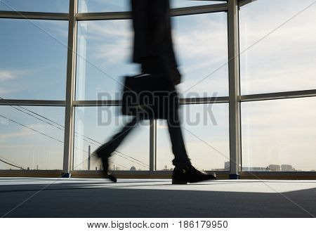 Blurred figure of businessman hurrying for work