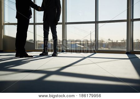 Two men greeting one another by handshake after negotiation