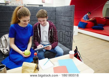 Two students discussing online data in touchpad while preparing homework