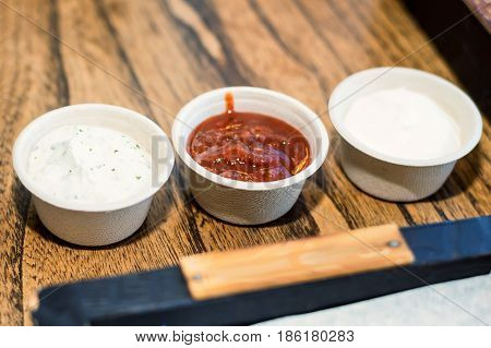 Fresh tomato, chili and mayonnaise sauces in white ceramic saucers