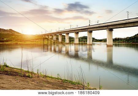High speed trains through the bridge dusk landscape