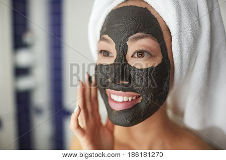 Closeup portrait of beautiful Asian woman applying face mask