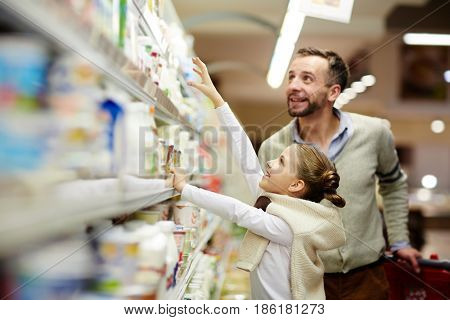 Happy family grocery shopping in supermarket: smiling man with daughter choosing dairy products from fridge in milk aisle