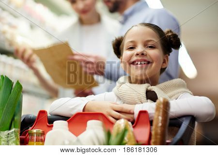 Portrait of cute little girl smiling happily while shopping in grocery store with family and looking at camera