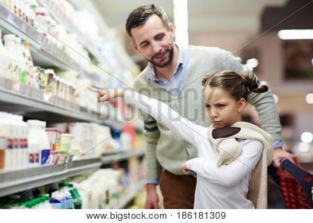 Family grocery shopping in supermarket: cute little girl pouting and pointing at milk bottle at dairy aisle with dad
